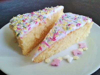 Old school sponge cake with white icing and multicoloured sprinkes